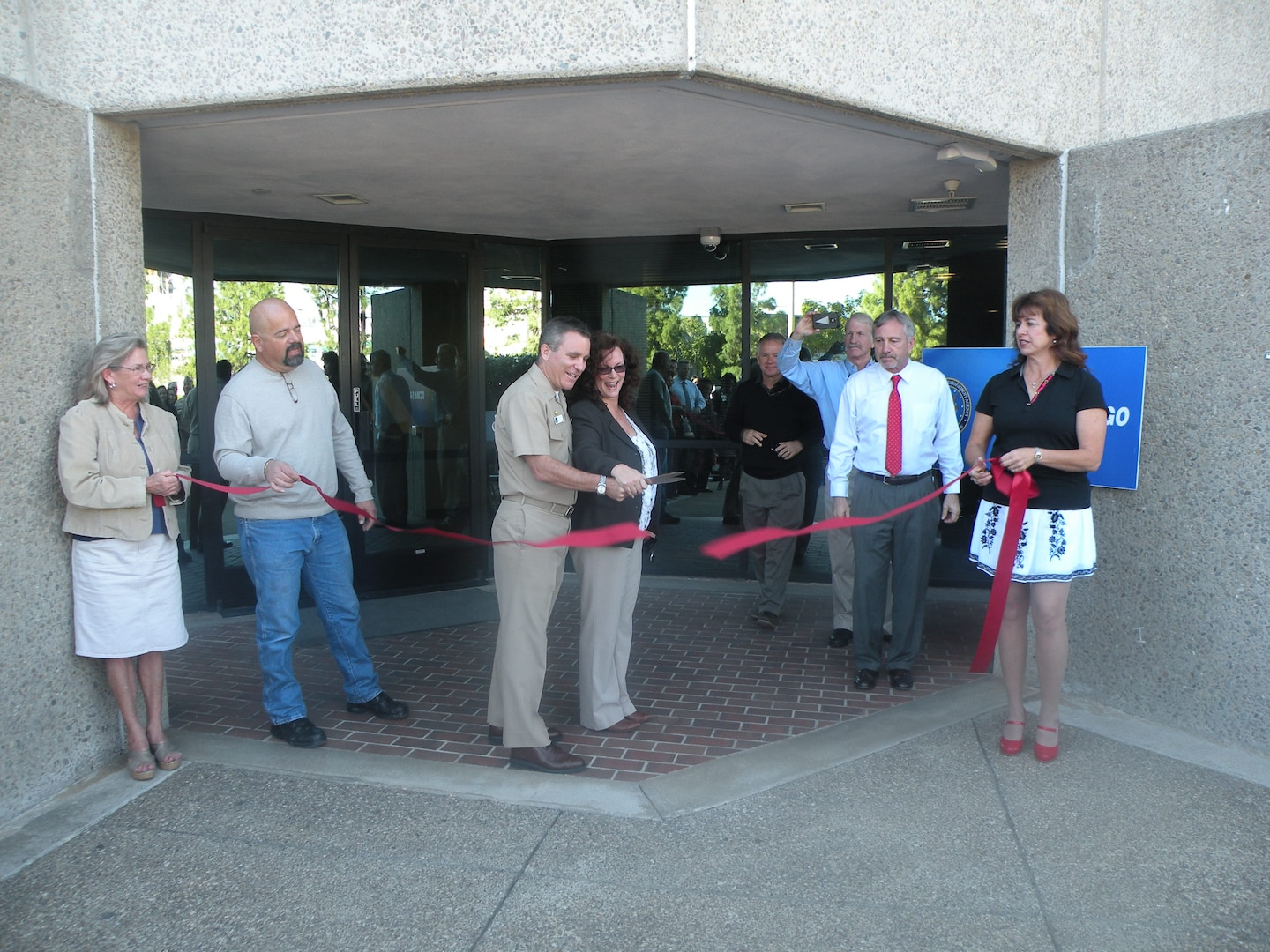 Navy Capt. Richard McCarthy, Defense Contract Management Agency San Diego commander, cuts the ribbon for the office's new facility. Three of the longest serving office employees — Jane Morales, Gabriel Tapia and Rachelle Munz — held the ribbon in celebration of their 75 combined years at the previous facility.