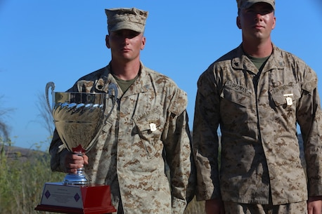 Sergeant Derrick Higgs and Cpl. Clayton Degnan, both with Co. C, 1st Battalion, 7th Marine Regiment, stand after receiving the Mitchell Cup and their annual rifle squad competition badges for winning the 2016 1st Marine Division Squad Competition award ceremony at Camp Pendleton, Calif., July 14, 2016. The Mitchell Cup was named after Cpl. Robert Mitchell, who received the Navy Cross for his heroic actions as a squad leader in Fallujah, Iraq. (U.S. Marine Corps photo by Lance Cpl. Shellie Hall)