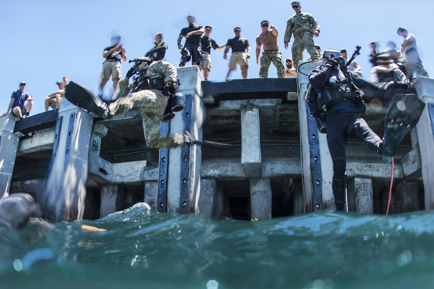 Army Pfc. Aaron Gaugler and Coast Guard Diver 2nd Class Kendall Smith enter the water as part of a pier maintenance training-mission.