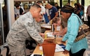 Tech. Sgt. Sonny Maldonado, 433rd Airlift Wing, Force Support Squadron, Airmen Family Readiness Technician, speaks with one of the Inactive Ready Reserve member July 9, 2016 as they process through the screening line at the IRR Muster at Joint Base San Antonio, Texas.