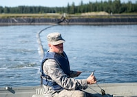 U.S. Air Force Airman 1st Class Troy Moncrief, a 354th Civil Engineering Squadron wastewater apprentice, uses a boat to inspect aeration equipment in ponds at the Eielson Air Force Base, Alaska, wastewater treatment plant July 15, 2016. The manufactured holding pond lined with thick black plastic hold millions of gallons of waste that is treated in a week's time after it enters the plant. (U.S. Air Force photo by Staff Sgt. Shawn Nickel)