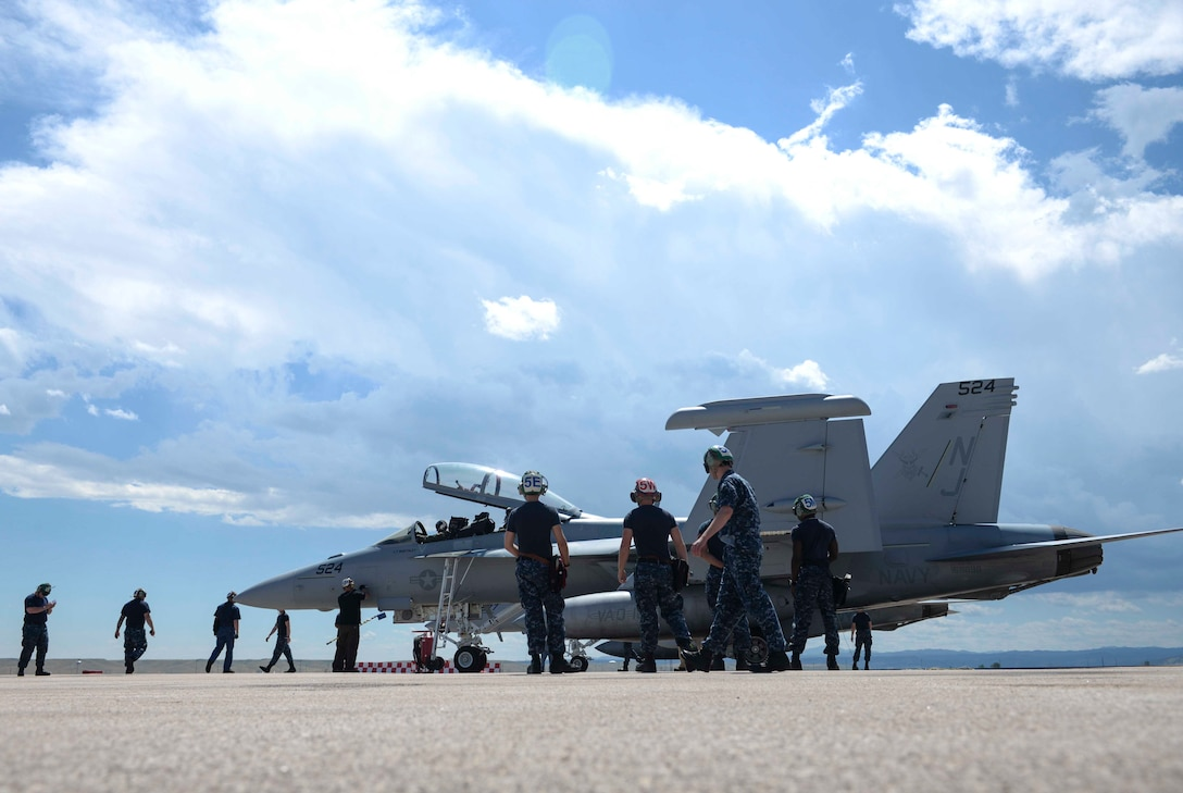 Navy maintenance personnel from Electronic Attack Squadron (VAQ) 129, assigned to Naval Air Station Whidbey Island, Wash., conduct a preflight check on an EA-18G Growler before a training flight at Ellsworth Air Force Base, S.D., July 15, 2016. Approximately 110 Sailors participated in the training, maintaining six EA-18G Growlers and focusing on airborne electronic attack tactics. (U.S. Air Force photo by Airman 1st Class Sadie Colbert/Released)