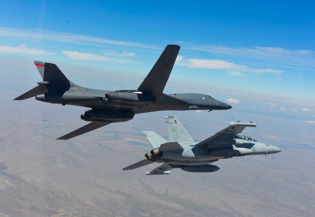 A B-1 bomber and EA-18G Growler bank to the left during a training sortie near Ellsworth Air Force Base, S.D., July 15, 2016. The training focused on further improving joint mission tactics between Air Force and Naval forces. (Courtesy Photo/Released)