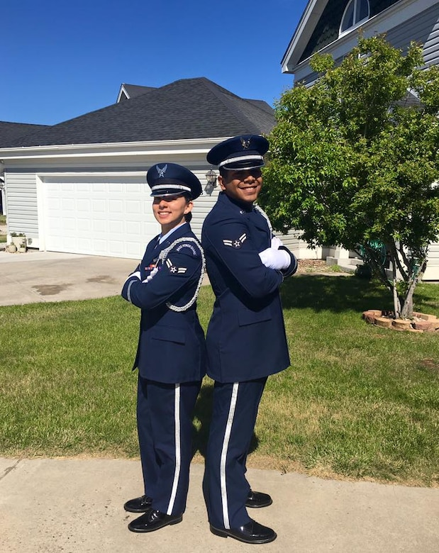 Airman 1st Class Alexandra Ayub, 90th Force Support Squadron missile chef, and her husband, Airman 1st Class Ozzie Galvan, 90th FSS fitness specialist, pose in their ceremonial guardsman uniforms outside of their F.E. Warren Air Force Base, Wyo., home. Both Airmen attended technical school together, and both joined the 90th Missile Wing Honor Guard. (Courtesy photo)