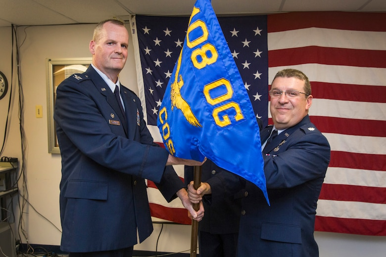 Lt. Col. Anthony Zissimos, right, accepts the 108th Operations Group guidon from Col. Thomas L. Coppinger, commander, 108th Wing Operations Group, New Jersey Air National Guard, assuming command of the 140th Cyber Operations Squadron at Joint Base McGuire-Dix-Lakehurst, N.J., July 17, 2016. Zissimos became the commander of the New Jersey Air National Guard's newest squadron, which is charged with monitoring cyber-attacks to the nation's computer networks, stopping the attacks, identifying the hackers, and repairing the damage. (U.S. Air National Guard photo by Master Sgt. Mark C. Olsen/Released)