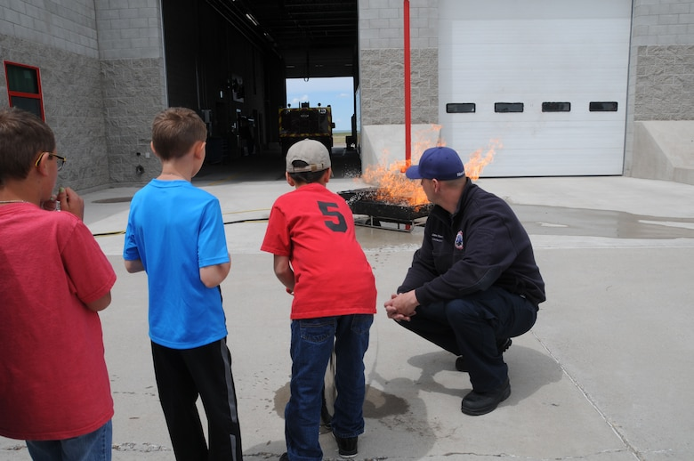 Montana Air National Guard Fire Department Lt. Jacob Harris observes as a child uses a fire extinguisher on a fire during a STARBASE tour of the station June 15, 2016. (U.S. Air National Guard photo/Senior Master Sgt. Eric Peterson)