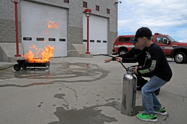 Montana Air National Guard Fire Department Lt. Jacob Harris shows a child how to operate a fire extinguisher on a fire during a STARBASE tour of the station June 15, 2016. (U.S. Air National Guard photo/Senior Master Sgt. Eric Peterson)