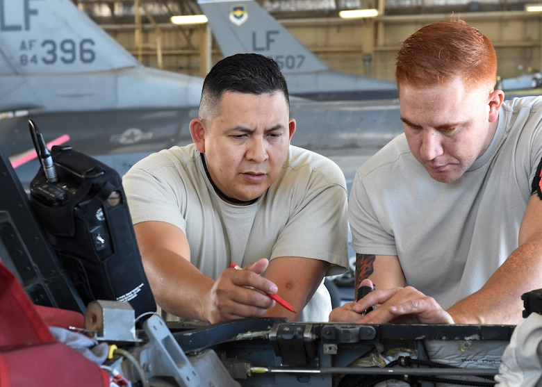 Master Sgt. Charles Ramirez and Tech. Sgt. Eric Garza, non-destructive inspection technicians, inspect an F-16D Fighting Falcon's longeron in the aircraft's canopy sill at Luke Air Force Base, Ariz., April 12, 2016. Ramirez and Garza are members of the Texas Air National Guard's 149th Fighter Wing, headquartered at Joint Base San Antonio-Lackland, Texas. (U.S. Air National Guard photo by 2nd Lt. Phil Fountain)