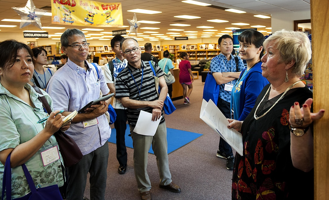"""Belinda Pugh, 18th Force Support Squadron resource librarian, explains a display during a tour of the library to local Okinawan librarians July 13, 2016, at Kadena Air Base, Japan. The purpose of the tour was for local Okinawan librarians to familiarize themselves with American culture so they can set up an """"American corner"""" in their libraries. (U.S. Air Force photo by Airman 1st Class Corey M. Pettis)"""
