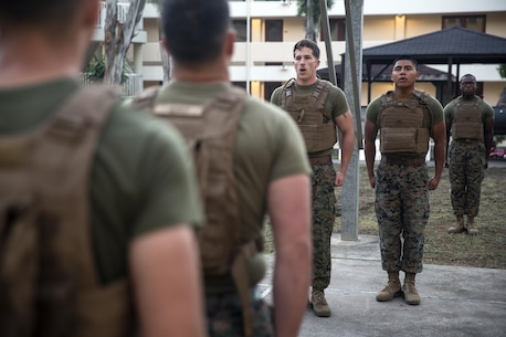 Cpl. Brandon Gaddis, and Cpl. Marcoantonio Gonzalez, the Corporals Course class First Sergeant and Gunnery Sergeant, stand in front of their formation as the class sings the Marines' hymn before physical training at Naval Air Station Sigonella, Italy, June 11, 2016.  Twenty-five Marines with Special Purpose Marine Air-Ground Task Force Crisis Response-Africa learned leadership skills, land navigation, sword and guidon manual, fire team and squad formations, and mentoring skills during the course.  (U.S. Marine Corps photo by Cpl. Alexander Mitchell/released)