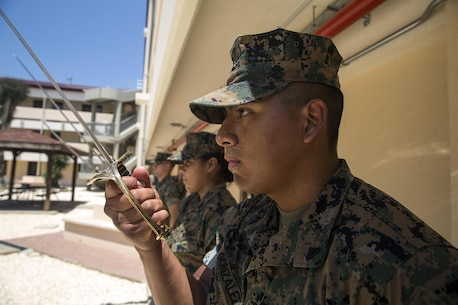 Cpl. Marcoantonio Gonzalez, the Corporals Course class Gunnery Sergeant, practices sword manual with his Marines at Naval Air Station Sigonella, Italy, June 11, 2016.  Twenty-five Marines with Special Purpose Marine Air-Ground Task Force Crisis Response-Africa learned leadership skills, land navigation, sword and guidon manual, fire team and squad formations, and mentoring skills during the course. (U.S. Marine Corps photo by Cpl. Alexander Mitchell/released)