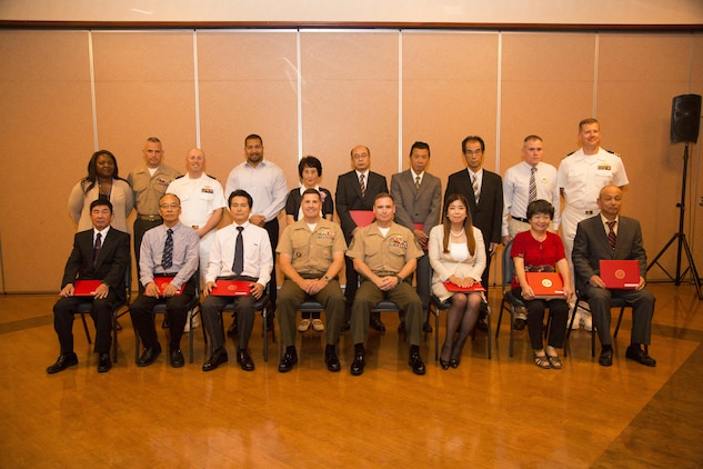 Retirees and members of Marine Corps Air Station Iwakuni leadership pose for a photo during a retirement ceremony at the Landing Zone in Club Iwakuni on MCAS Iwakuni, Japan, July 15, 2016.  The ceremony acknowledged the appreciation for the retirees' hard work and dedication toward the installation's success over the years.  (U.S. Marine Corps photo by Lance Cpl. Jacob Farbo)