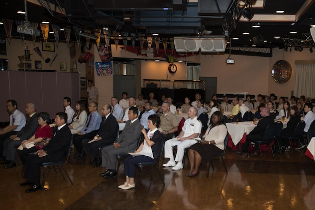 Retirees and guests attend a retirement ceremony at the Landing Zone inside Club Iwakuni at Marine Corps Air Station Iwakuni, Japan, and listen as U.S. Marine Corps Col. Robert V. Boucher, station commanding officer, gives a speech July 15, 2016. The ceremony acknowledged the appreciation of the retirees' hard work over the years. (U.S. Marine Corps photo by Lance Cpl. Joseph Abrego)