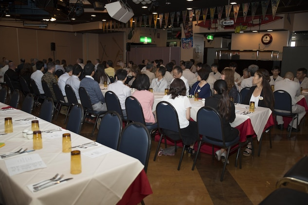 Guests attend a retirement ceremony at the Landing Zone inside Club Iwakuni at Marine Corps Air Station Iwakuni, Japan, and listen as U.S. Marine Corps Col. Robert V. Boucher, station commanding officer, gives a speech July 15, 2016. The ceremony acknowledged the appreciation for the retirees' hard work and dedication toward the installation's success over the years.  (U.S. Marine Corps photo by Lance Cpl. Joseph Abrego)