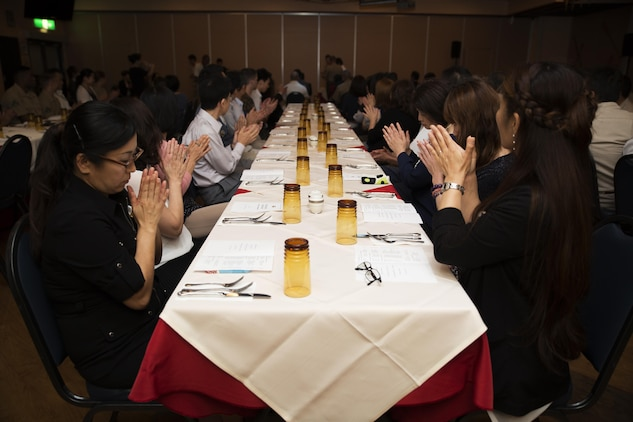 Guests attending a retirement ceremony at the Landing Zone inside Club Iwakuni at Marine Corps Air Station Iwakuni, Japan, applaud as Master Labor Contract and Indirect Hire Agreement employees receive certificates of appreciation July 15, 2016. The ceremony acknowledged the appreciation of the retirees' hard work over the years. (U.S. Marine Corps photo by Lance Cpl. Joseph Abrego)