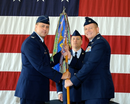 Col. John Nichols, 14th Flying Training Wing Commander, passes the 14th Operations Group guidon to Col. Stan Lawrie, the new 14th OG Commander, during a change of command ceremony July 15 at Columbus Air Force Base, Mississippi. (U.S. Air Force photo/Sharon Ybarra)