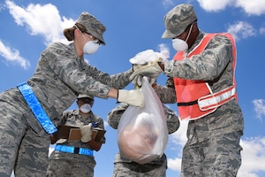 21st and 50th Force Support Squadron Airmen bag, tag and record a mock body part during a search and recovery exercise at Peterson Air Force Base, Colo., July 14, 2016. The search halted when an item was found to make sure all of the simulated remains and personal belongings were properly recorded. (U.S. Air Force photo by Airman 1st Class Dennis Hoffman)