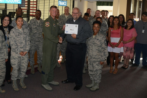 "Roger Kuhlmann, 47th Force Support Squadron military and manpower flight chief, accepts the ""XLer of the Week"" award from Col. Thomas Shank, left, 47th Flying Training Wing commander, and Chief Master Sgt. Erica Shipp, 47th Mission Support Group superintendent, here, July 13, 2016. The XLer is a weekly award chosen by wing leadership and is presented to those who consistently make outstanding contributions to their unit and Laughlin. (U.S. Air Force photo/Airman 1st Class Brandon May)"