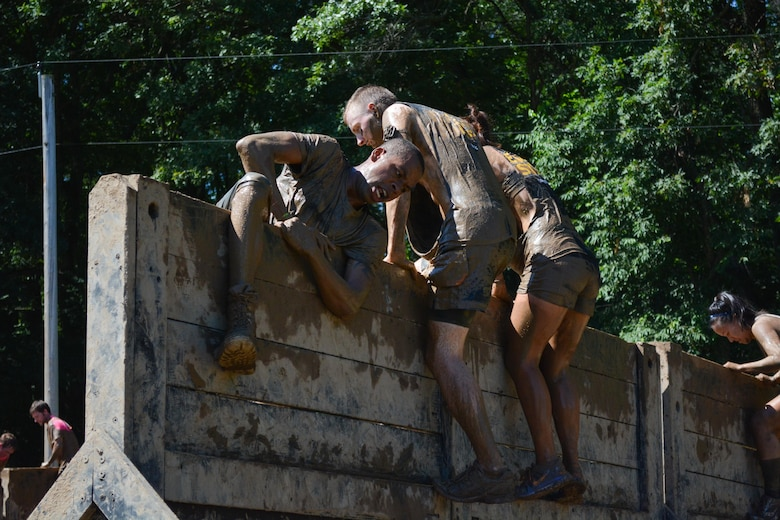 """HUGO, Minn. -- The Army Reserve team comprised of Soldiers from the 103rd Sustainment Command (Expeditionary) help each other over the Army Reserve-sponsored, nine-foot """"Berlin Wall"""" during the Tough Mudder held in Hugo, Minnesota, July 17, 2016. This 10-12 mile, military-style obstacle course has challenged more than one million competitors since its inception in 2010, challenging the participant's strength and stamina while building camaraderie."""