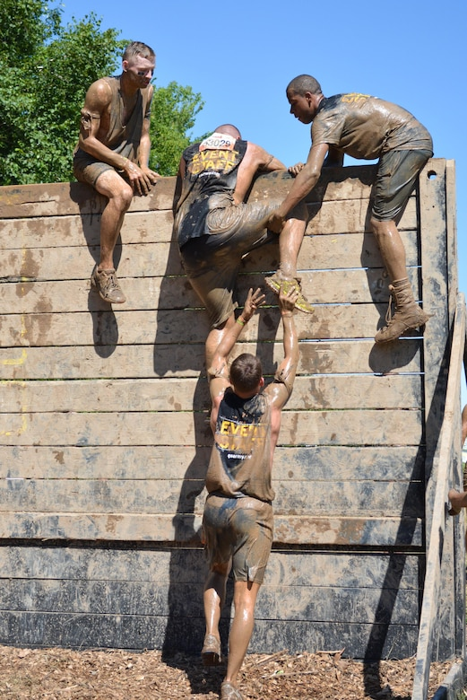 """HUGO, Minn. -- Army Reserve Soldiers from the 103rd Sustainment Command (Expeditionary) help each other over the nine foot """"Berlin Wall"""" during the Tough Mudder held in Hugo, Minnesota, July 17, 2016.  The Army Reserve-sponsored, 10 to 12 mile military-style obstacle course has challenged more than one million competitors since its inception in 2010, testing the participants' strength and stamina while building camaraderie."""