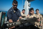 Gunners Mate 1st Class Christopher Lamotte dismounts a .50-caliber gun to demonstrate how to properly perform maintenance on it to Iraqi sailors assigned to Iraqi Swift Boat (P-308) during a monthly Iraqi bilateral exercise. Lamotte is assigned to the Arleigh Burke-class guided-missile destroyer USS Russell. Photo by MC2 Torrey W. Lee