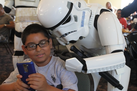 A Star Wars Storm Trooper takes a selfie with a child during Recruiting Station Los Angeles' Family Day at Naval Base Ventura County Port Hueneme, July 16, 2016. During the family day, volunteers from the 501st Legion Southern California Garrison dressed up as Star Wars characters, interacting with families. (U.S. Marine Corps photo by Staff Sgt. Alicia R. Leaders/Released)