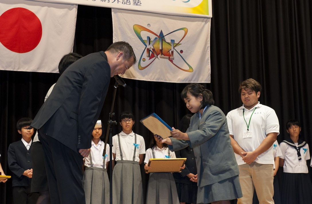 Iroha Ganaha, Kadena Elementary School fifth grade student, receives the 18th Wing Special Award from U.S. Air Force Col. Paul Oldham, 18th Mission Support Group commander, during the 19th annual Kadena Language Institute English Contest July 14, 2016, at the Kadena Rotary Town Plaza, Okinawa, Japan. The 18th Wing Special Award winner is hand-chosen by the 18th MSG commander based on their performance. (U.S. Air Force photo by Airman 1st Class Lynette M. Rolen)