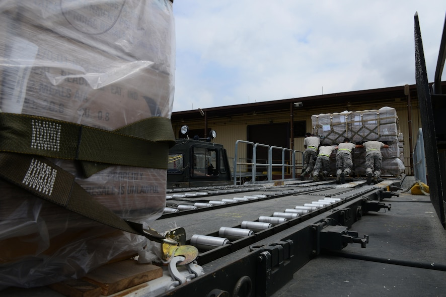 U.S. Airmen from the 728th Air Mobility Squadron push pallets of meals, ready to eat onto a roller platform July 19, 2016, at Incirlik Air Base, Turkey.  After an extended loss of commercial power to the base, supplies, including food, water and fuel, were delivered to sustain missions supporting Operation Inherent Resolve. (U.S. Air Force photo by Tech. Sgt. Caleb Pierce)