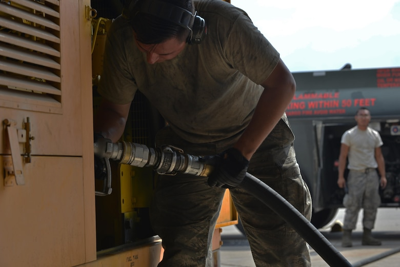 U.S. Air Force Airman 1st Class Trenton Beard and Eduardo Reyes, 39th Logistics Readiness Squadron fuels specialists, refuel a generator July 19, 2016, at Incirlik Air Base, Turkey. Fuels specialists maintain and operate petroleum equipment and facilities. (U.S. Air Force photo by Senior Airman John Nieves Camacho)