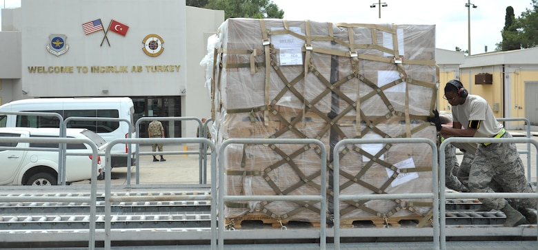 U.S. Airmen from the 728th Air Mobility Squadron push a pallet of meals, ready to eat onto rollers, July 19, 2016, at Incirlik Air Base, Turkey. Due to an extended loss of commercial power, food, fuel and other supplies were sent to Incirlik to sustain missions in support of Operation Inherent Resolve. (U.S. Air Force photo by Tech. Sgt. Joshua T. Jasper)