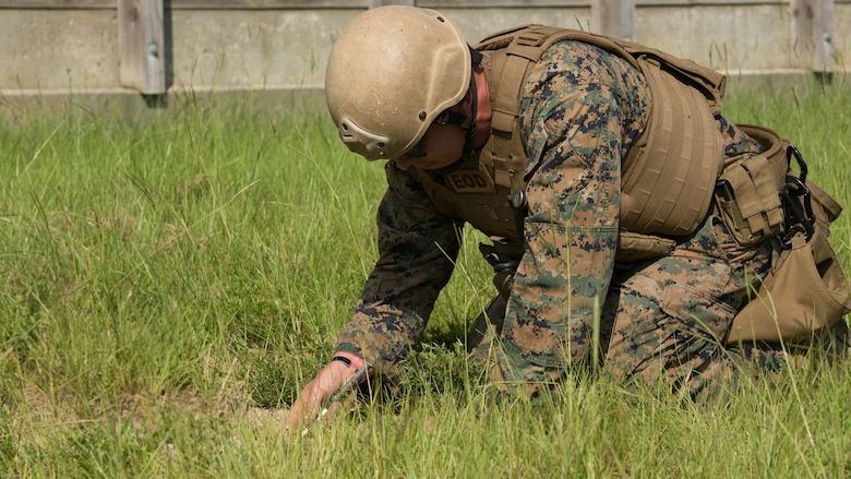 Sgt. David Jones, an explosive ordnance disposal team leader with 2nd EOD Company, 8th Engineer Support Battalion, uncovers part of a controlled improvised explosive device during a training exercise at Marine Corps Base Camp Lejeune, N.C., July 19, 2016. The unit conducted the training to test the effects of different types of excavation charges.