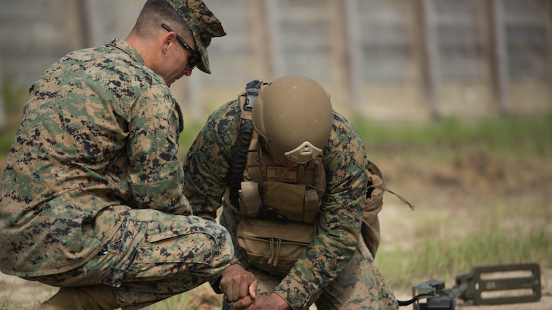 Sgt. Derek Turner, an explosive ordnance disposal technician with 2nd EOD Company, 8th Engineer Support Battalion, observes as Sgt. Anthony Carbajal digs around a controlled improvised explosive device during a training exercise at Marine Corps Base Camp Lejeune, N.C., July 19, 2016. The unit conducted the training to test the effects of different types of excavation charges.