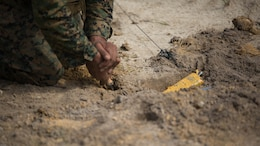 Sgt. Anthony Carbajal, an explosive ordnance disposal team leader with 2nd EOD Company, 8th Engineer Support Battalion, removes dirt surrounding a controlled improvised explosive device during a training exercise at Marine Corps Base Camp Lejeune, N.C., July 19, 2016. The unit conducted the training to test the effects of different types of excavation charges.