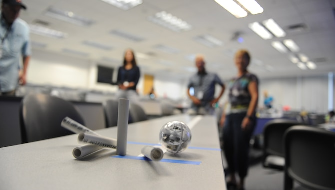 Teachers Roger Tucker from the Colorado Springs School and Deborah Andrews from Timberview Middle School, both of Colorado Springs, watch as the robot strikes its makeshift pins to finish an exercise in robots, via the application of math, angles and robotic commands. The U.S. Air Force Academy hosted its annual STEM teacher boot camp July 19-21, bringing in 110 K-12 teachers from across Colorado and several other states, to improve STEM teaching skills. (U.S. Air Force photo by John VanWinkle)
