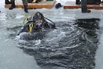 Hospital Corpsman 1st Class Aaron Christensen, assigned to Puget Sound Naval Shipyard, prepares to dive under ice during an annual ice diving course in Lone Butte, Canada. The course is taught by Coast Guard instructors attached to the Naval Diving and Salvage Training Center. Navy Photo by Cmdr. Hung Cao