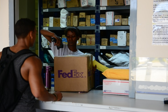 U.S. Air Force Senior Airman Adrianne Riley, 39th Communications Squadron postal clerk, delivers mail to a customer July 20, 2016, at Incirlik Air Base, Turkey. Due to an extended loss of commercial power, members of the Official Document Center operated under limited lighting conditions. (U.S. Air Force photo by Tech. Sgt. Caleb Pierce)