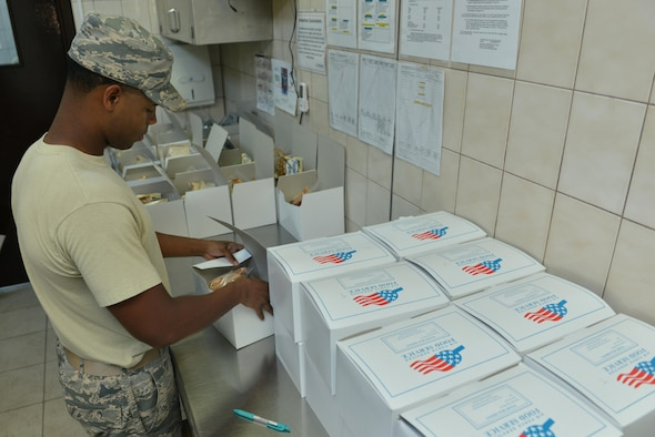 U.S. Air Force Airman 1st Class Jordan Eaden, 39th Force Support Squadron fitness journeyman, prepares boxed meals in the Sultan's Inn Dining Facility July 21, 2016, at Incirlik Air Base, Turkey. The meals were delivered to Airmen posted around the installation who are unable to go to the dining facility. (U.S. Air Force photo by Senior Airman John Nieves Camacho)