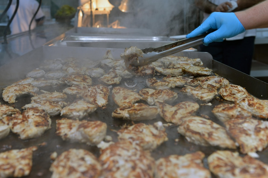 A Sultan's Inn Dining Facility employee grills a plethora of chicken breasts in the Sultan's Inn Dining Facility July 21, 2016, at Incirlik Air Base, Turkey. Grilled chicken breasts, along with pot roast, chicken a la king and steak and cheese sandwiches were some of the featured entrees. (U.S. Air Force photo by Senior Airman John Nieves Camacho)