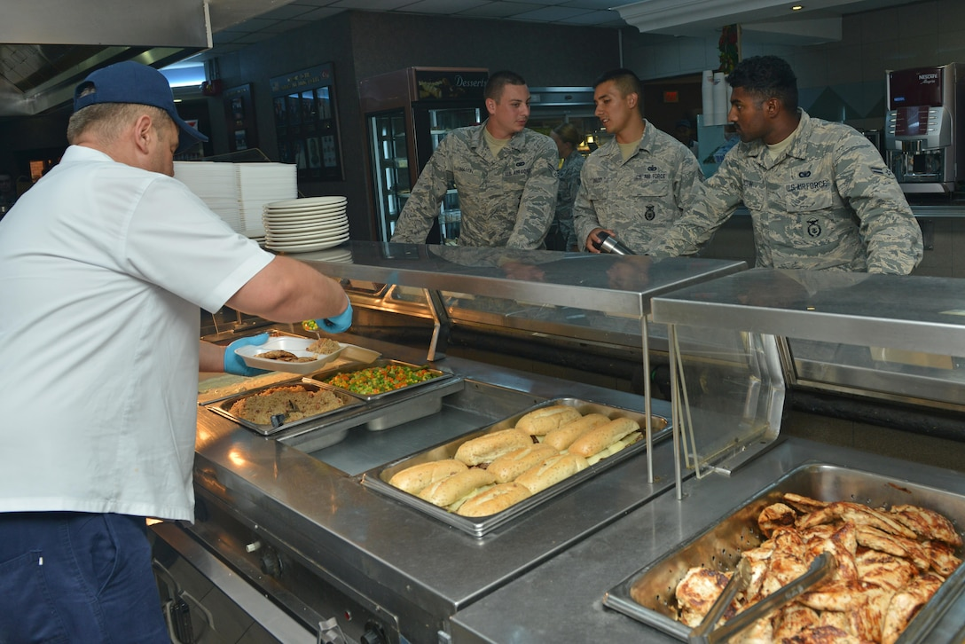 A Sultan's Inn Dining Facility employee serves food for Airmen July 21, 2016, at Incirlik Air Base, Turkey. Services employees prepare, cook and serve food for dining facility patrons. (U.S. Air Force photo by Senior Airman John Nieves Camacho)