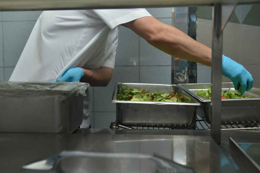 A Sultan's Inn Dining Facility employee creates salad trays July 21, 2016, at Incirlik Air Base, Turkey. Salads consist of a variety of vegetables to include lettuce, tomatoes and cucumbers. (U.S. Air Force photo by Senior Airman John Nieves Camacho)
