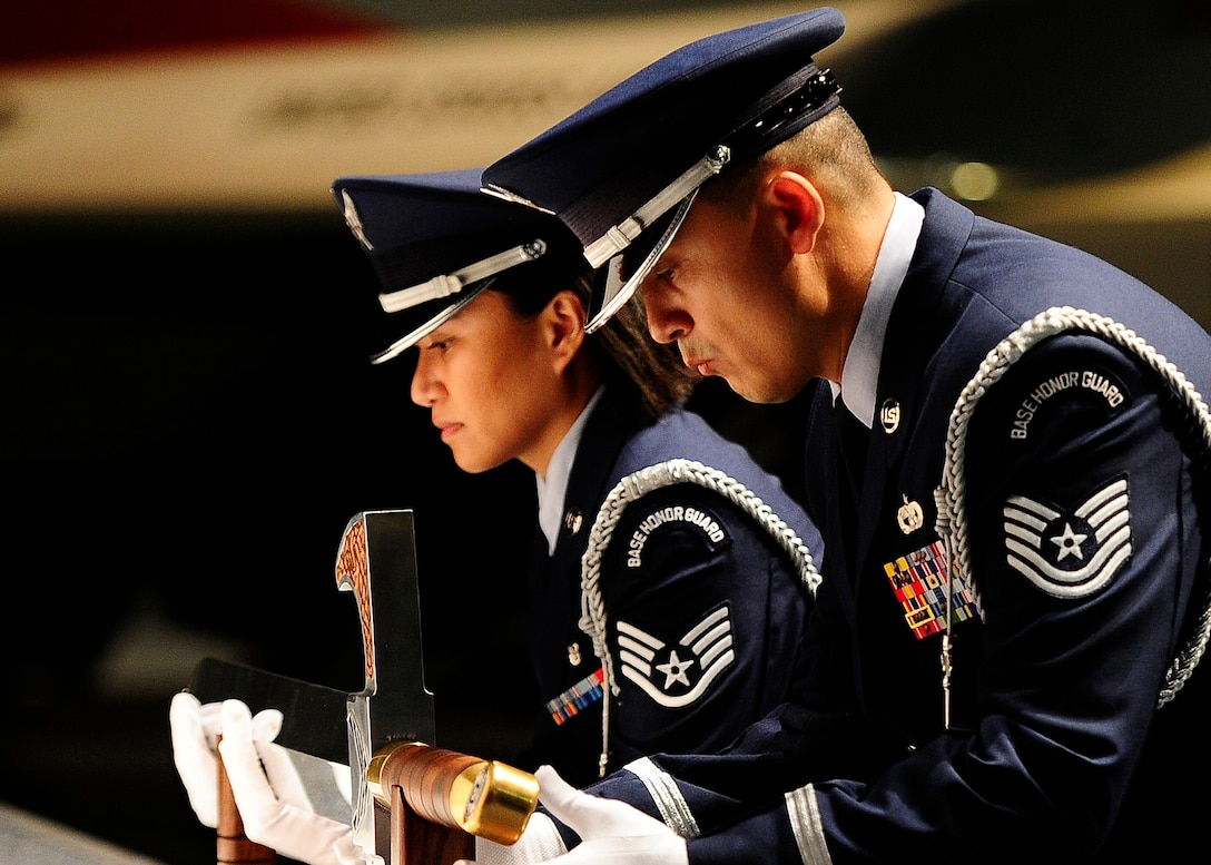 U.S. Air Force Honor Guard members Tech. Sgt. Juan Garcia and Staff Sgt. Annzen Salvador lift the sword used for the Order of the Sword ceremony at the Museum of Aviation in Warner Robins, Ga., July 13, 2016. The Order of the Sword is an honor awarded by NCOs of a command to recognize individuals they hold in high esteem and for their contributions to the enlisted corps. (U.S. Air Force photo/Tech. Sgt. Stephen D. Schester)