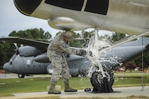 Master Sgt. Matthew Tabor, a 314th Maintenance Group quality assurance chief inspector, breaks a bottle to christen an H-21B helicopter in Heritage Park at Little Rock Air Force Base, Ark., July 14, 2016. Volunteers from the 314th MXG refurbished, transported and installed the H-21B static display. (U.S. Air Force photo/Senior Airman Harry Brexel)