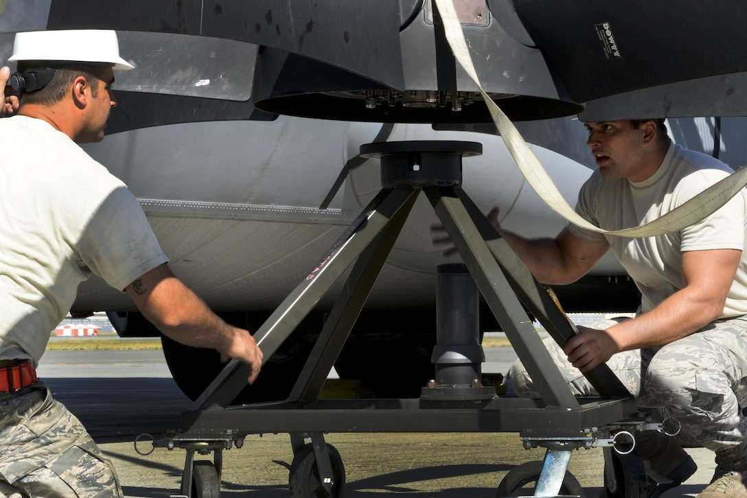 U.S. Air Force Staff Sgt. Kyle Chambasian, left, and U.S. Air Force Senior Airman Aaron Swible, 19th Aircraft Maintenance Squadron aerospace propulsion journeymen, secure a damaged C-130J propeller onto a stand July 21, 2016, at Joint Base Elmendorf-Richardson, Alaska. The de-ice boot of the propeller failed, which is a critical piece of equipment when flying at high altitudes and in Alaska. (U.S. Air Force photo by Senior Airman Stephanie Serrano)