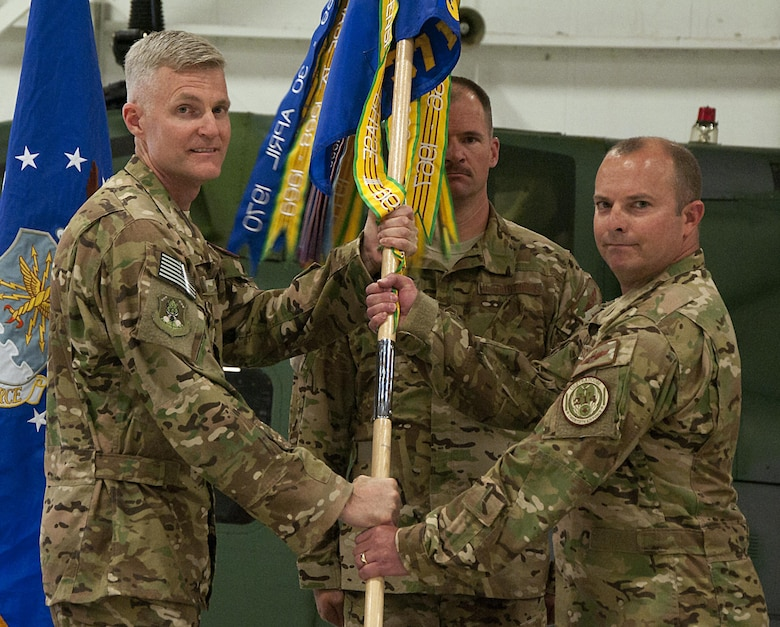 Col. David Smith, 582nd Helicopter Group commander, passes the guidon to Lt. Col. James Cline, 37th Helicopter Squadron commander, during the 37th HS change-of-command ceremony at F.E. Warren Air Force Base, Wyo., July 21, 2016. The ceremony signified the transition of command from Lt. Col. Todd Ivener to Cline. (U.S. Air Force photo by Senior Airman Brandon Valle)