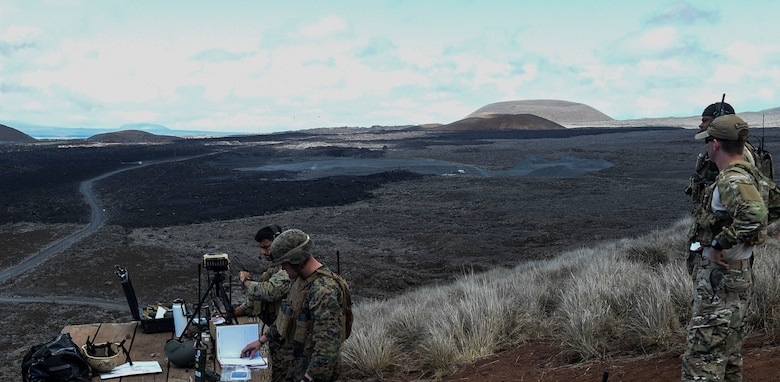 Marines from III Marine Expeditionary Forces call in close air support as a combat controller from the 353rd Special Operations Group oversees the training as a joint terminal attack controller instructor during RIMPAC to strengthen relationships and interoperability, Pohakuloa Training Area, Hawaii, July 15, 2016. (U.S. Air Force photo by 2nd Lt. Jaclyn Pienkowski/Released)
