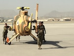 Members of the Afghan air force wheel out a new MD-530 Cayuse Warrior helicopter at the 438th Air Expeditionary Wing/Train, Advise, Assist Command-Air in Kabul, Afghanistan, July 16, 2016.