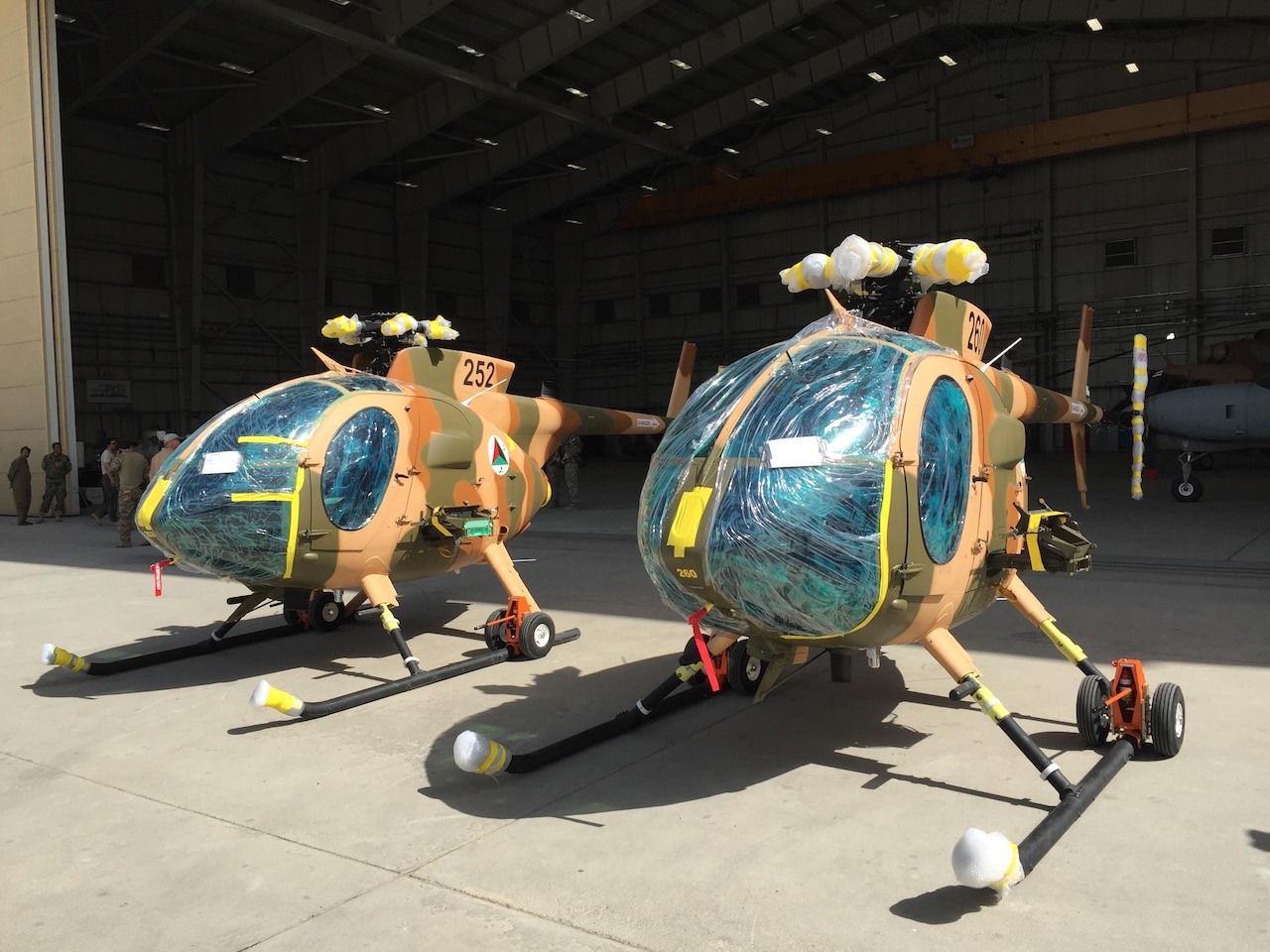 Two new MD-530 Cayuse Warrior helicopters, still with protective wrap on them, are seen at the 438th Air Expeditionary Wing/Train, Advise, Assist Command-Air in Kabul, Afghanistan, July 16, 2016. DoD photo by Lisa Ferdinando