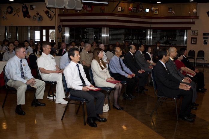 Master Contract Labor and Indirect Hire Agreement employees at the Landing Zone inside Club Iwakuni at Marine Corps Air Station Iwakuni, Japan, await the presentation of their awards July 15, 2016. A retirement ceremony was held in honor of the MLC and IHA employees' hard work over the years. (U.S. Marine Corps photo by Lance Cpl. Joseph Abrego)