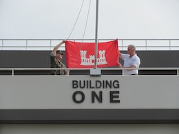 """Passersby Marine Corps Air Station Iwakuni Building One on July 16 may have had to look twice when they saw the U.S. Army Corps of Engineer's bright red castle flag flying over the Marine headquarters.  Marine Col. Robert Boucher, commanding officer, MCAS Iwakuni, raised the USACE flag over the headquarters building with Lee Seeba, former resident engineer, Iwakuni Resident Office, under the joyful eyes of several Iwakuni Resident Office employees.  Boucher flew the engineer castle in Iwakuni as a """"thank you"""" to the Corps' Iwakuni Resident Office for a job well done, after completing a particularly intricate project by deadline.  Bert Pechhold, current resident engineer, Iwakuni Resident Office, said the transformation that is occurring at MCAS Iwakuni could not be possible without the leadership and support from Boucher and his staff.  """"This achievement symbolizes that spirit of cooperation and partnership between the Army and Marines,"""" Pechhold said.  Seeba is currently the area engineer for the Japan District's Okinawa Area Office."""