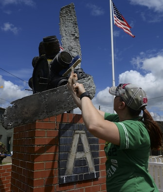 U.S. Air Force Tech. Sgt. Tracy Thorpe, 373rd Training Squadron KC-135 avionics instructor, cleans a monument on display July 17, 2016, at the RAF Rougham Tower Museum in Bury St. Edmunds, England.  Volunteers from the Air Force Sergeants' Association visited the museum to perform minor landscaping. (U.S. Air Force photo by Staff Sgt. Micaiah Anthony)